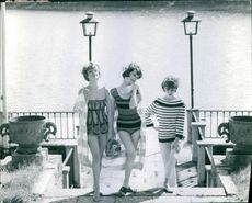 Women in bathing suits and posing at stairs, holding a cloth and modeling.  1961