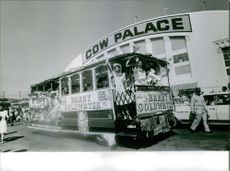 Women waving from the vehicle, cow palace in background. 1964