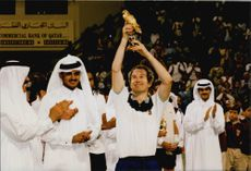 John McEnroe holds up the golden eagle he received from Shaikh Tamim after winning Qatar tennis tournament
