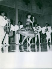 Woman performing on stage with other artists.