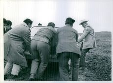 Lorne Greene with other people push the car, got stuck in mud.
