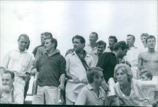 1960  Claude Brasseur standing with men and woman Saint Tropez town in France.