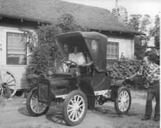 Woman sitting in La Gitana car with one-cylinder Cadillac engine, while man is starting the engine in the rear.