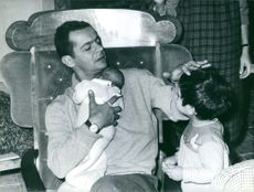 Serge Reggiani holding a baby while touching the head of a young child looking at him.