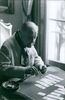 William Somerset Maugham sitting while playing cards on the table, 1965.