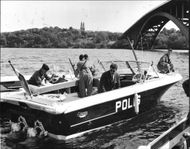 Marinepolice in Riddarfjarden by the Stockholm West Bridge takes care of a civilian boat.