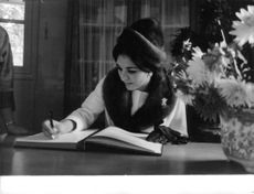 Farah Pahlavi writing in a diary.