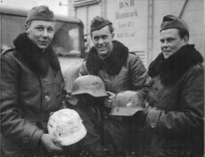 Three Red Cross, members of the repatriated assistance Corps from Vienna holding German helmets as a souvenir.