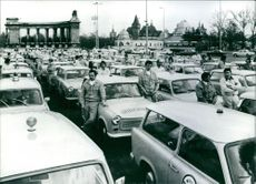 """Hungary's highway repairmen - known as """"Yellow Angeles"""" - line up for a parade in Budapest. They work for the Hungarian Automobile Club and drive Trabant """"mini"""" cars. 1977."""