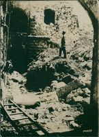 Vintage photo of a man standing in front of a ruin stone building in France. 1914