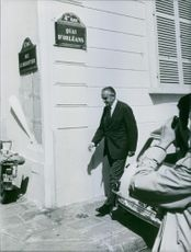 A photo of an American Democratic politician, businessman, and diplomat William Averell Harriman walking on sidewalk while a camera man taking pictures on him.