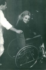 Sandra Milo sitting sitting in  wheelchair, smiling.