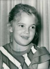 Drew Blythe Barrymore as a child smiling.