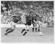 Trevor Putney and Gordon Strachan are fighting for the ball
