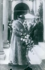 Wilhelmina of the Netherlands is walking, while she hold a bunch of flower