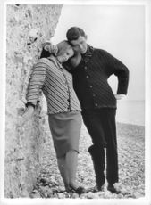 A couple posing against a rock in the seashore.