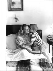 A boy kissing on chick of Jeanne Moreau.