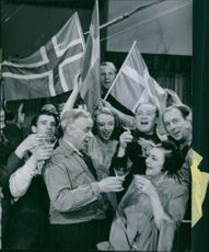 People holding flags and celebrating together, drinking.