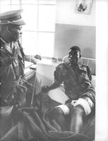 An injured soldier on a hospital bed, talking to another soldier in kongo. 1967