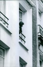 Woman standing on balcony and looking down.
