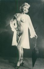 A naked woman standing and posing.