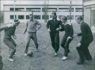 1945 Men playing football, and practicing.