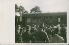 People gathered in street and looking towards the people in a huge vehicle during WWI.
