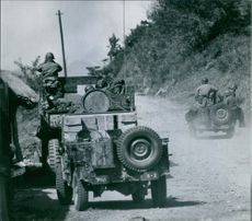 Soldiers with their vehicles in street during war. 1950.
