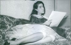 Jacqueline Boyer sitting on the bed.