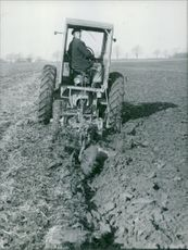 Man driving tractor in field, looking back.