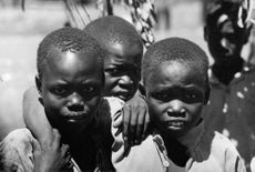 Three kids looking into the camera from Kenya.