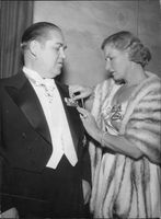 "Johan Jonatan ""Jussi"" Björling`s wife putting badge on his chest."