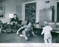 Taina Elg playing with her child and a gentleman looking from sofa.