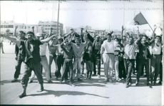 Demonstrators raiding their hands during a rally in the street.