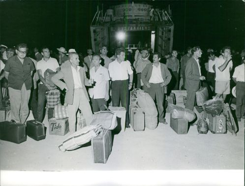 People waiting for a train in a railway station.