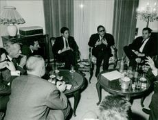 Mehdi Ben Barka sitting with people in discussion.