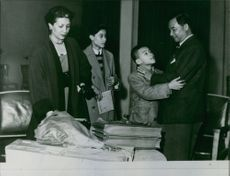 Man standing and talking to his son, his wife and another son standing behind looking at them and smiling.
