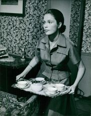 Ulla Jacobsson walking while holding a tray.