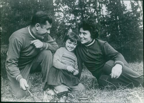 The family sitting on the grass field. August 15, 1962