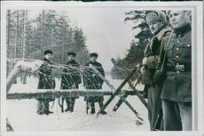 Soldiers standing on both side of barbed wire border.