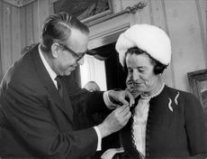 Swedish scout manager Bengt Junker attaches the honor to Rose Kennedy's suit jacket.