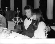 Herb Alpert holding a trophy with his wife Sharon Mae Lubin.