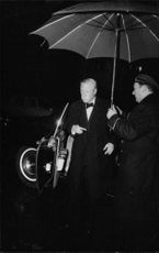 The Duke of Windsor got off the automobile, escorted with umbrella while raining