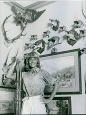 1967 A photo of a French actress of the 1950s and the early 1960s Dany Robin smiling and posing in a room wherein portraits of animals are being displayed.