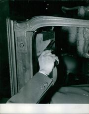A gun being held by a man, under the table.