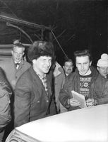 A man in a fur hat and his buddy holding documents being surrounded by other people looking into the camera.