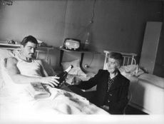 An old woman having a drink with the patient lying on the hospital bed during Algerian war.