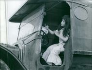 A child girl siting in the driver seat in the vehicle, moving her hands as if she is singing.   1962