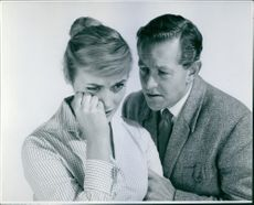 A man holding and talking to a woman crying.