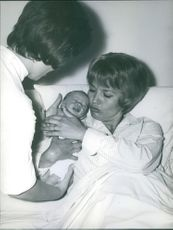 Nurse giving baby to Liselotte Pulver.